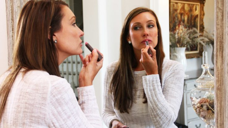 Kim Comisar applies lipstick at her home in New Albany, OH. Comisar was one of a record number of patients who got lip implants in 2015.